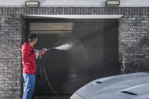 Man Pressure Washing Garage Door
